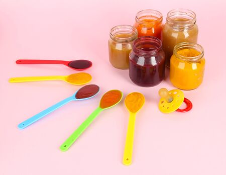 Baby puree in spoons with nipple on pink background photo