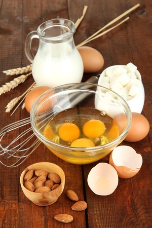 Broken egg in bowl and various ingredients next to them on wooden table close-up photo
