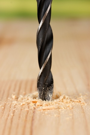 Close-up image of drilling hole on wooden plank, on bright background photo