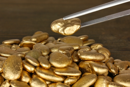 tough luck: Tweezers holding golden stone on wooden background