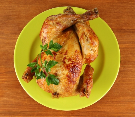 Roasted whole chicken on a green plate on wooden background photo