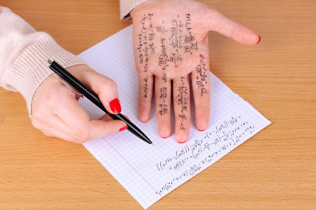 Write cheat sheet on hand on wooden table close-up Stock Photo - 20647531