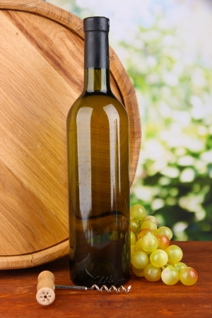 Composition of corkscrew and bottle of wine, grape, wooden barrel  on wooden table on bright background photo