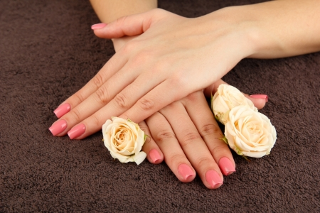 Woman hands with pink manicure and flowers, on color background Stock Photo - 20647444