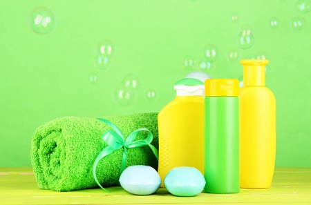 Baby cosmetici, asciugamano e sapone sul tavolo in legno, su sfondo verde