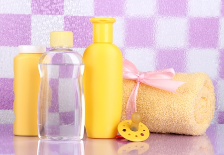 Baby cosmetics and towel in bathroom on violet tile wall background Stock Photo - 20647272