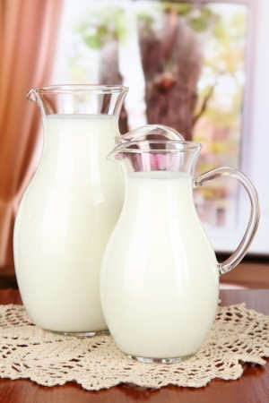 pasteurized: Pitchers of milk on table in room