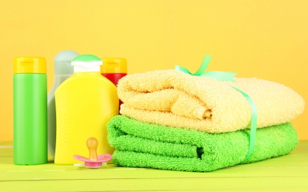 Baby cosmetics and towels on wooden table, on yellow background photo