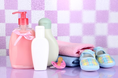 Baby cosmetics and towels  in bathroom on violet tile wall background Stock Photo - 20647310