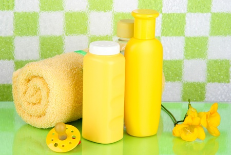 Baby cosmetics and towel in bathroom on green tile wall background photo