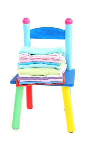 Small and colorful chair with baby clothes isolated on white Stock Photo - 20647029