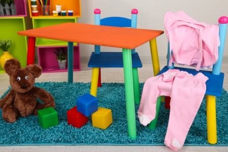 Small and colorful table and chairs with baby clothes photo