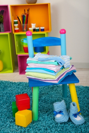 Small and colorful chair with baby clothes photo