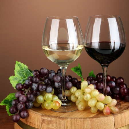 Glasses of red and white wine, grape on  wooden barrel, on color background photo