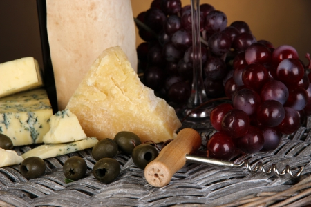 Refined still life of wine, cheese and grapes on wicker tray close-up photo