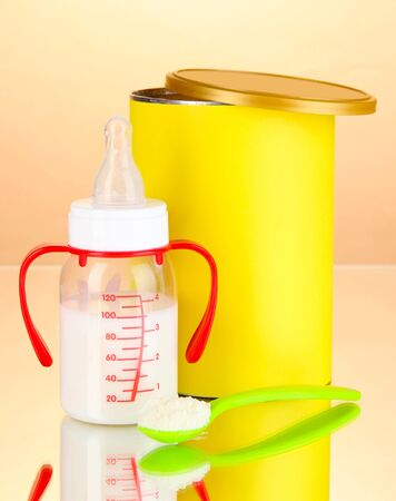 fondo para bebe: Botella con la leche y los alimentos para beb�s en el fondo de color beige