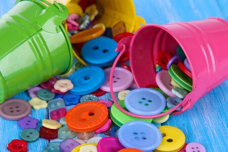 Colorful buttons strewn from buckets close-up photo