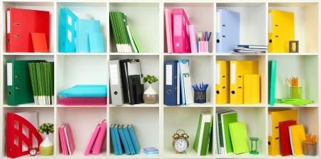 White office shelves with different stationery, close up photo