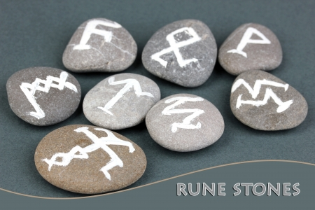 Fortune telling  with symbols on stones on grey background Stock Photo - 20653127