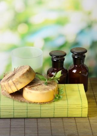 schiuma di sapone: Fatta a mano e sapone ingredienti per la fabbricazione del sapone sulla stuoia di bamb�, su sfondo verde Archivio Fotografico