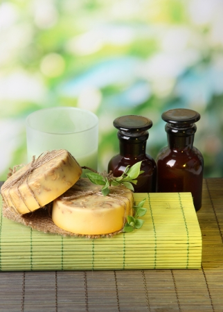 making up: Hand made soap and ingredients for soap making on bamboo mat, on green background Stock Photo