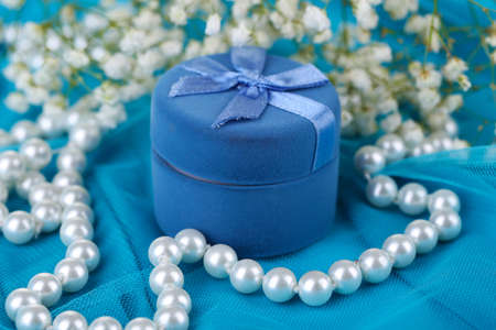 Flowers  and engagement ring on blue cloth photo
