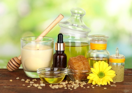 Fragrant honey spa with oils and honey on wooden table on natural background photo