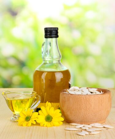 Useful pumpkin seed oil on wooden table on natural background photo