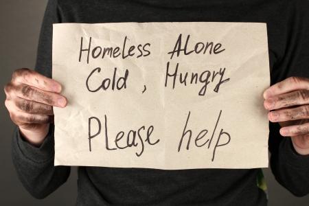 vagabundos: hombre sin hogar pide ayuda, sobre fondo negro close-up Foto de archivo