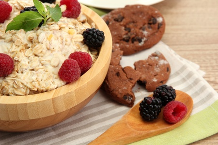 tasty oatmeal with berries, on wooden table photo