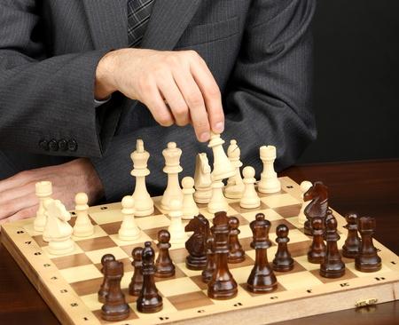 jugando ajedrez: Hombre de negocios joven que juega al ajedrez sobre fondo negro