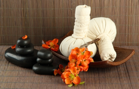 Herbal compress balls for spa treatment and spa stones on bamboo background photo