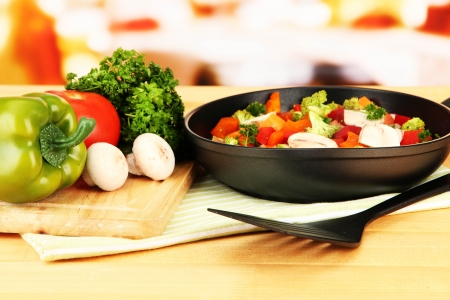 asian cooking: Vegetable ragout in pan,  on wooden table on bright background