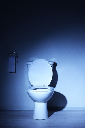 Toilet bowl in a bathroom with blue light photo