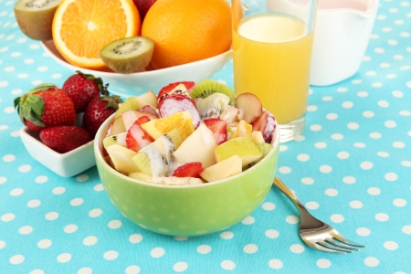 Useful fruit salad of fresh fruits and berries in bowl on tablecloth close-up photo