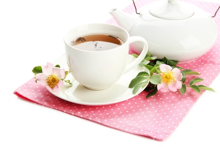 Cup and teapot of herbal tea with hip rose flowers, isolated on white photo