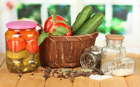 Tasty green cucumbers and red tomatoes in basket, on wooden table on bright  background photo