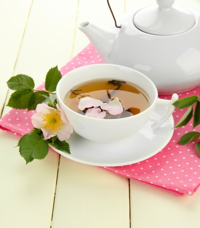 Cup and teapot of herbal tea with hip rose flowers on white wooden table photo