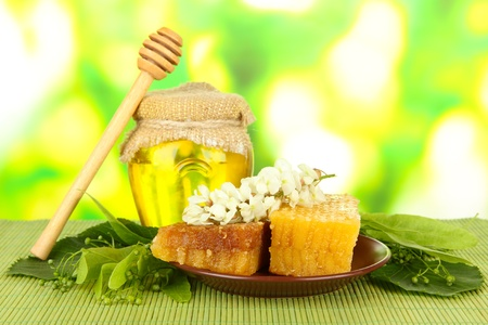 Jar of honey and honeycombs with flowers of lime, acacia on color bamboo mat on bright background photo