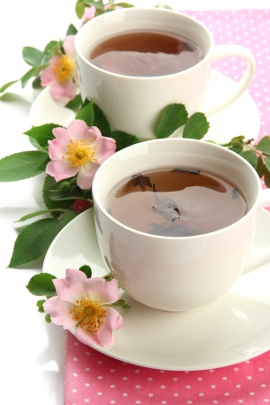 Cups of herbal tea with hip rose flowers, isolated on white photo