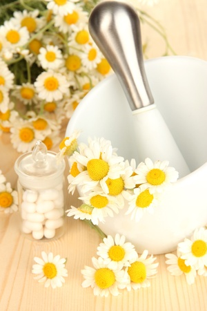 Medicine chamomile flowers on wooden table photo