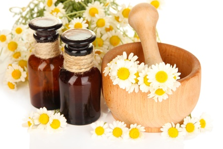 Essential oil and chamomile flowers in mortar close up photo
