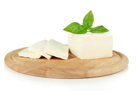 Queso de oveja leche con albahaca en la tabla de cortar, aislado en blanco