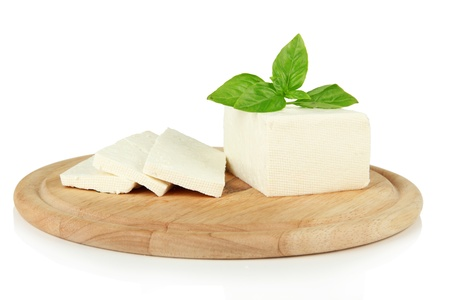 Sheep milk cheese with basil on cutting board, isolated on white Stock Photo