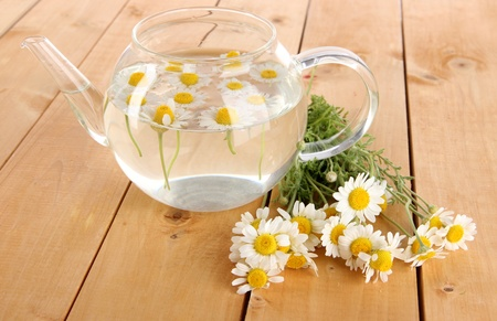 Glass teapot with chamomile on wooden table photo