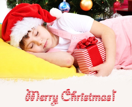 The little girl fell asleep with gift in their hands in festively decorated room photo
