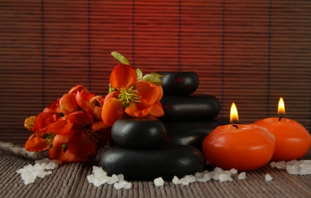 Spa stones with flowers and candles on bamboo background photo