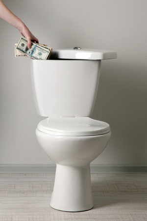 Hand hides money in toilet tank in a bathroom Stock Photo - 20811996