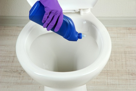 Woman hand with spray bottle cleaning a toilet bowl in a bathroom photo
