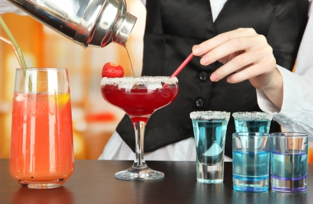 Barmen hand with shaker  pouring cocktail into glass, on bright background photo